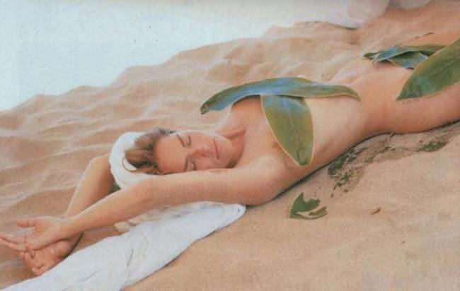 Голая лежит на песке прикрыта листьями пальмы.