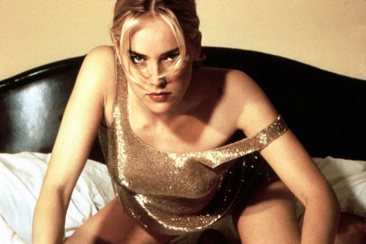 Шэрон стоун фото золотом платье сидит на диване, поддавшись вперед, левая бретелька платья немного спущена
