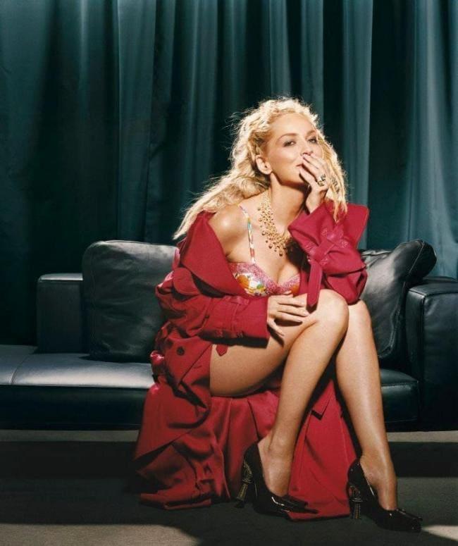 В красном распахнутом пеньюаре, черные туфли на высоком каблуке, сидит на диване.