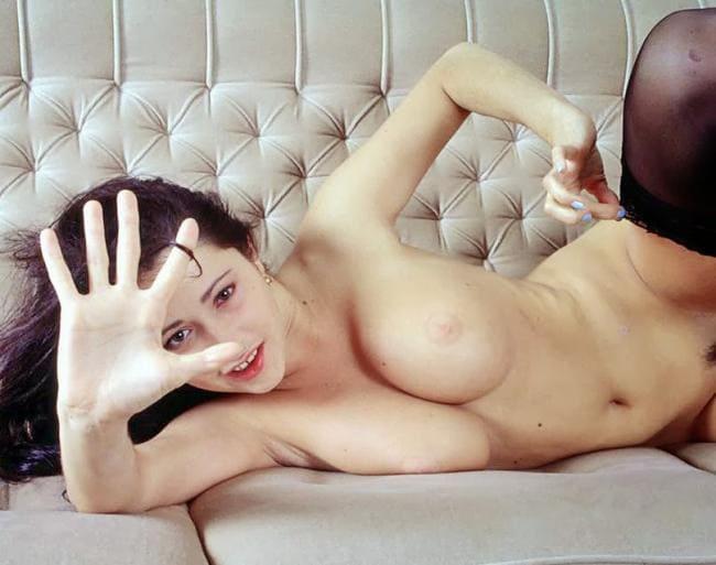 фото Любовь Тихомирова ню лежит голая показываю шикарную грудь, кокетливо выставив ладонь другой рукой оттягивает чулок, губы накрашены красной помадой, рот эротично приоткрыт
