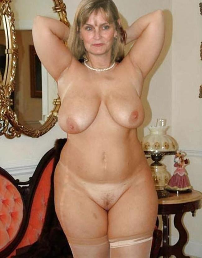 Женщина за 50 стоит в комнате в чулках, руки подняты видно подмышки