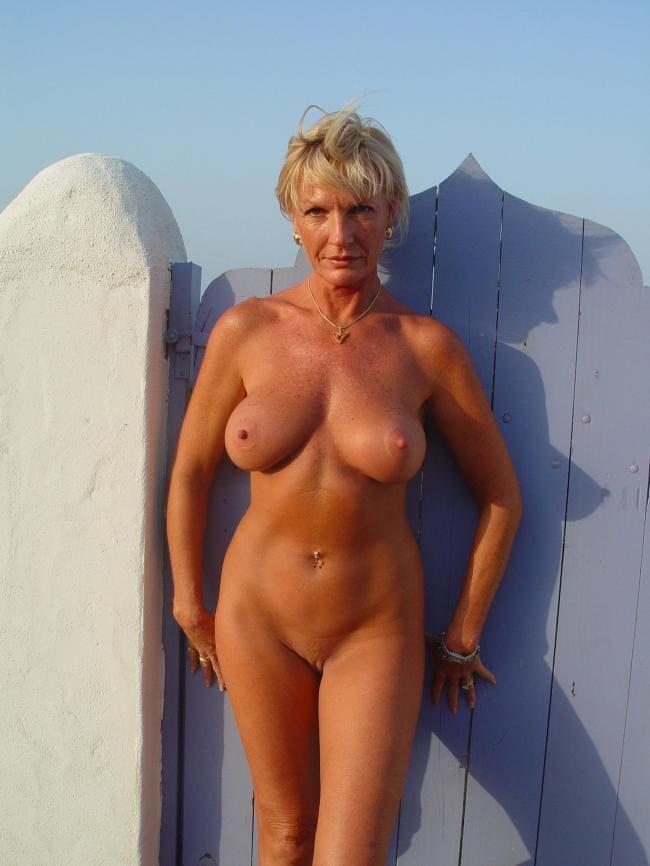 Зрелые голые сиськи тетки фото. Шикарная тетка за 50 стоит у забора, фигура очень красивая
