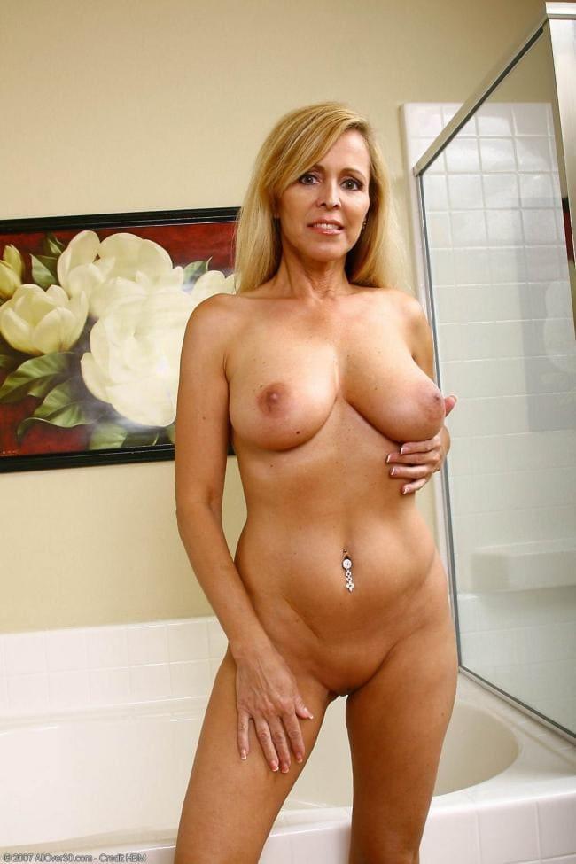 Зрелая блондинка стоит возле ванной чисто выбритая с пирсингом в пупке