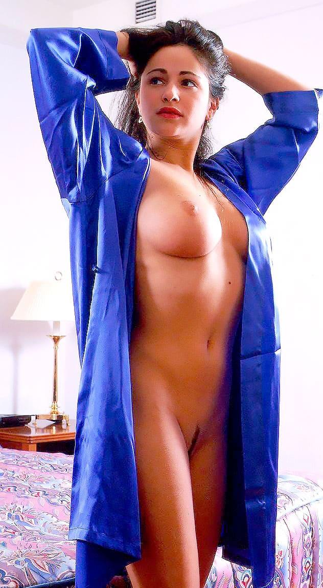 Любовь Тихомирова ню стоит рядом с кроватью в распахнутом халате синего цвета, руки подняты на затылок придерживают волосы, виден правый бок, с голой сиськой и пизда аккуратно бритая в стрижку.