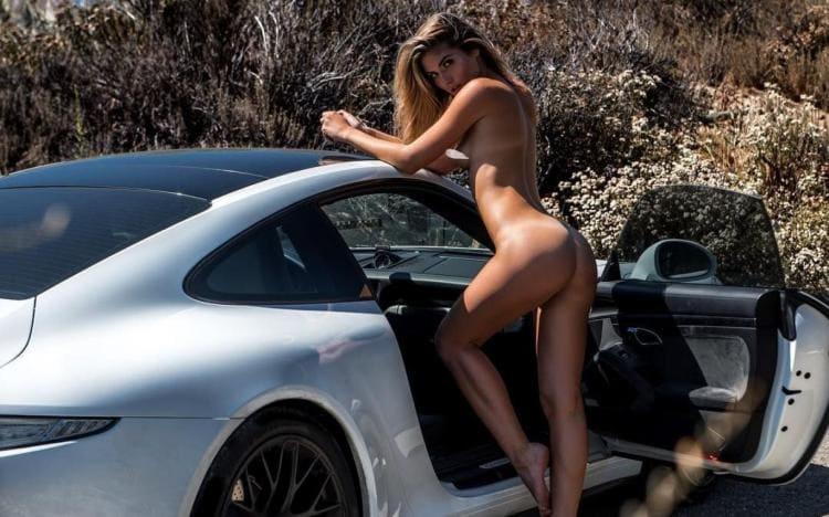Голая красотка возле автомобиля.