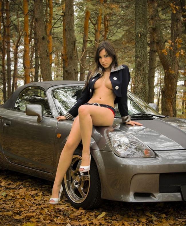 голая девушка сидит на машине в накинутой курточке на капоте в босоножках