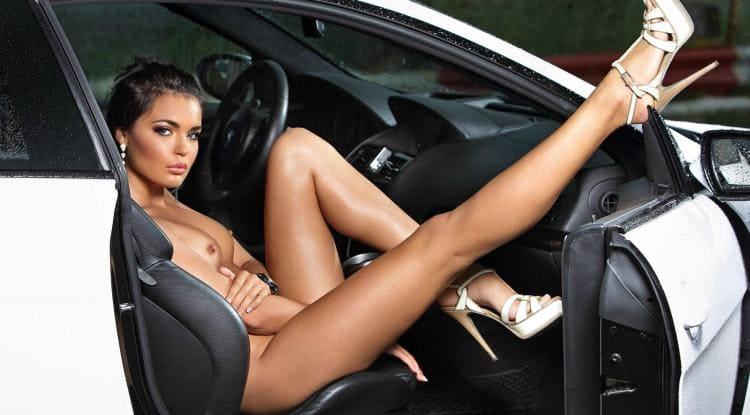 Голая девушка в машине сидит на сиденье ногу закинула на дверцу, босоножки высокий каблук