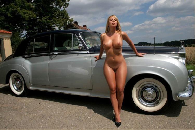 Голая блондинка с красивой фигурой стоит возле шикарного ретро-автомобиля.