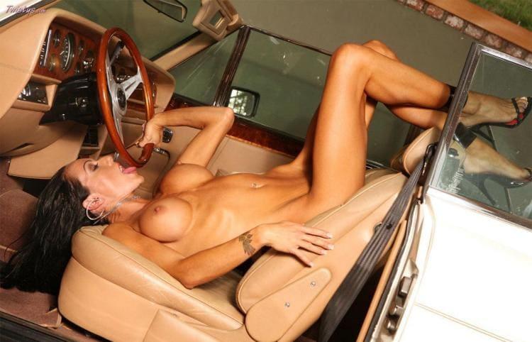 Голая дама лежит на сиденье водителя облизывает руль, ноги задраны на сиденье, босоножки высокий каблук, очень сексуалное фото.