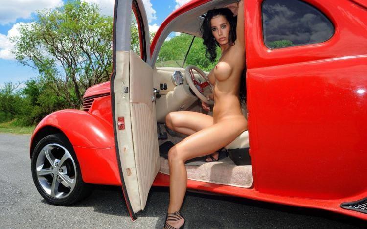 голая красотка сидит в красном ретро-автомобиле
