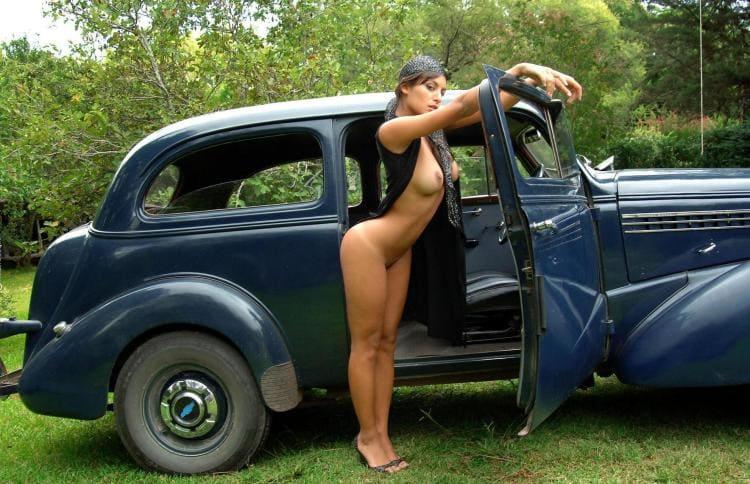 Голая красотка с шикарной фтгурой возле черного ретро-автомобиля