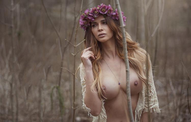 Красивая девушка с обнаженной грудью на природе