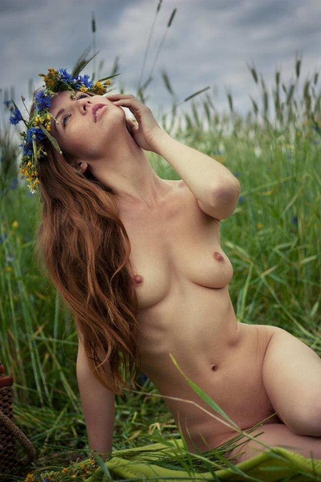 Красивая девушка с каштановым длинным волосом голая сидит в траве задумалась