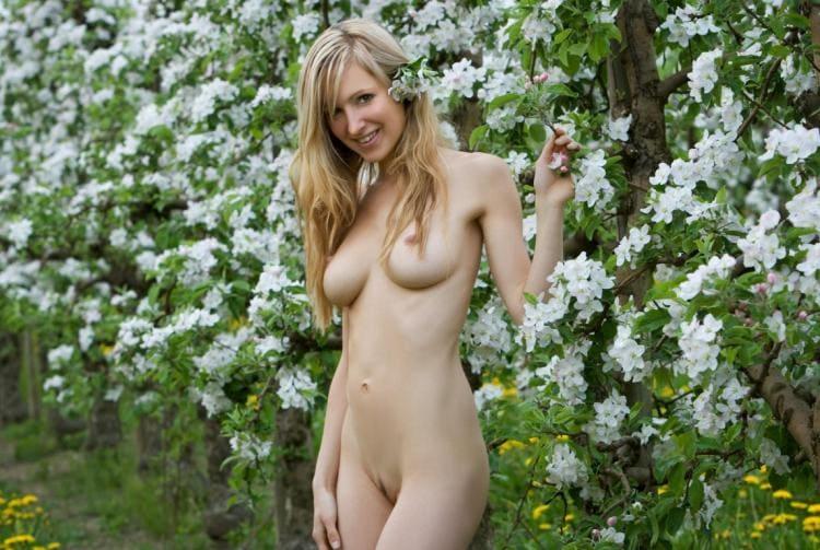 Голая блондинка стоит в цветущем саду