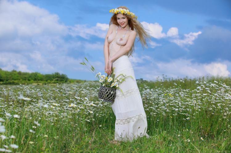 Голая девушка с длинными русыми волосами стоит а цветущем поле.
