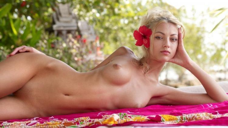 Шикарная голая блондинка лежит на боку, фигура ммм, в волосах красный цветок, видна бритая подмышка
