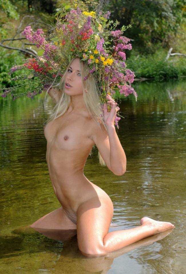 Блондинка голая стоит на коленях в воде