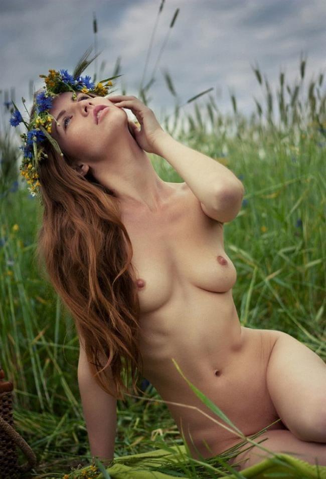 Красивая шатенка с длинным волосом голая сидит в траве, смотрит задумчиво в небо