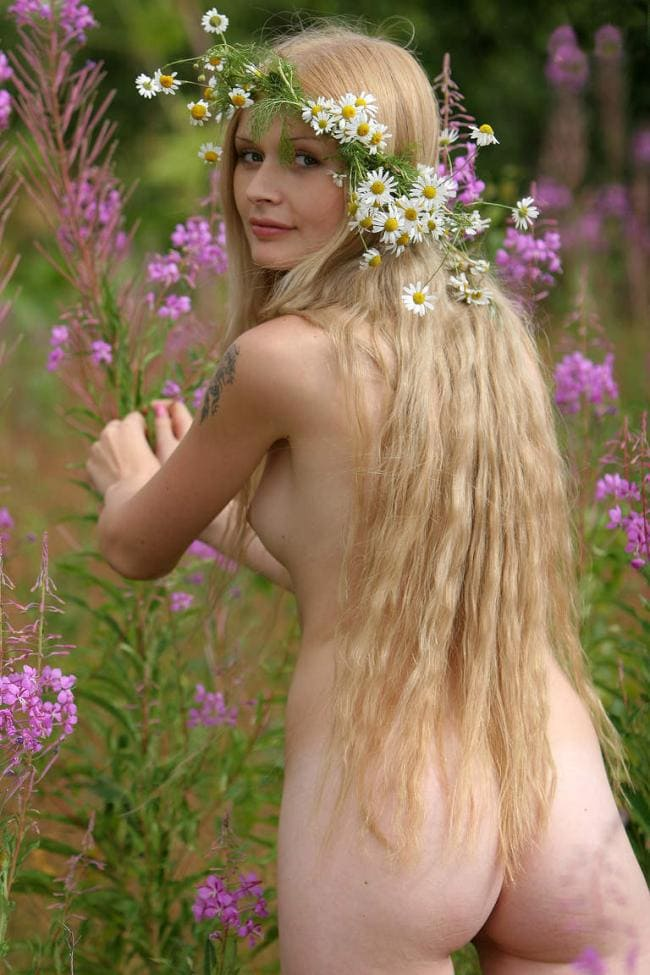 Красивая голая блондинка стоит развернувшись попой в поле