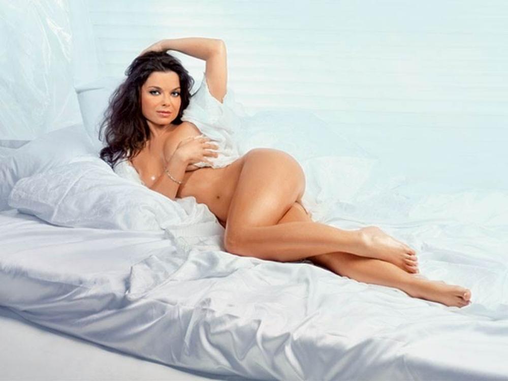 Голая Наташа Королева лежит на кровати на белой постели, левая рука немного прикрывает сиськи, нога на ногу закинута, красивые бедра