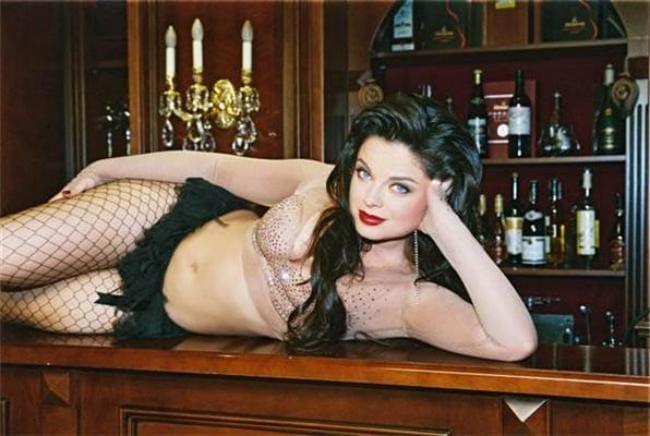Полуобнаженная лежит на барной стойке колготки в крупную сетку