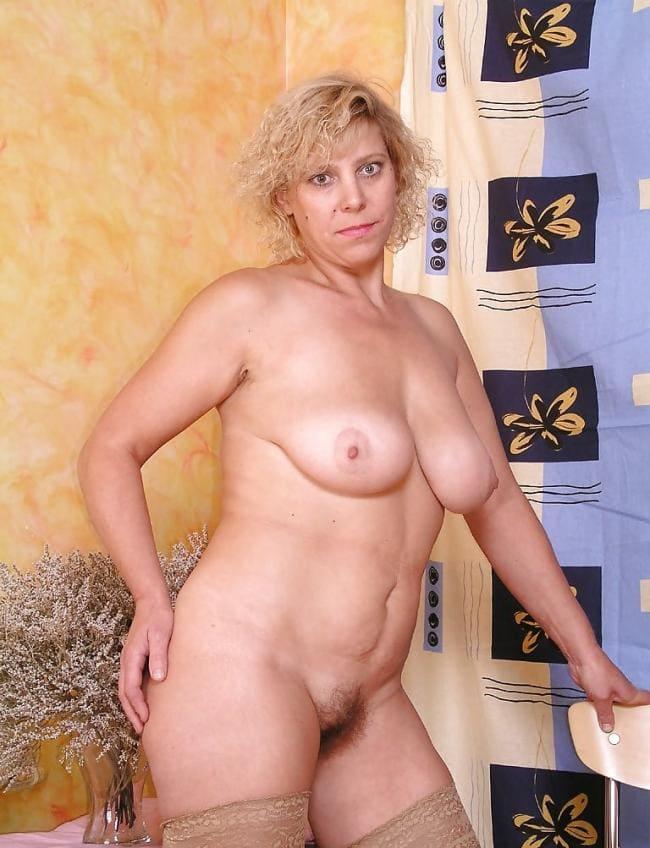 голые зрелые тетки фото женщины стоящей у занавешенного окна в чулках телесного цвета держится за стул и призывно смотрит