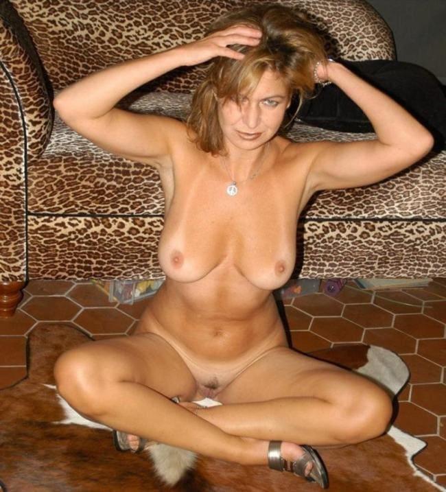 голые зрелые тетки фото загорелой русоволосой женщины за 50 полностью обнажена, стройная фигура, на местах трусов и лифчика видна белая не загорелая кожа, сидит сложив ноги на полу и смотрит развратно