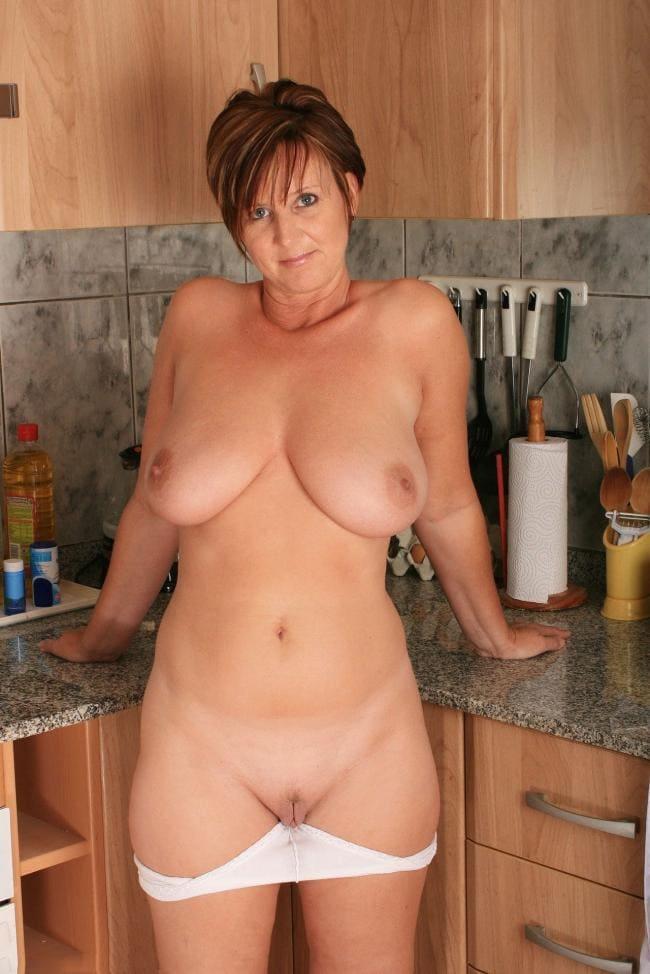 голые зрелые тетки фото красивой брюнетки с короткой стрижкой на кухне. Белые трусы спущены видна бритая пизда. Отклонилась назад и сексуально смотрит