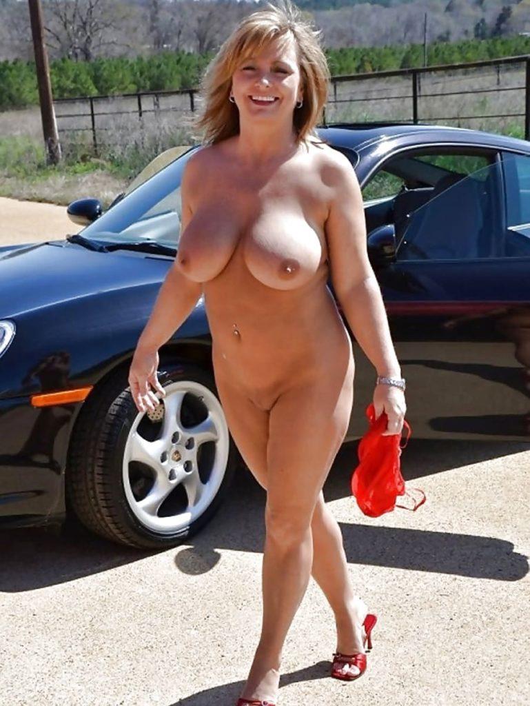 голые зрелые тетки фото идущей от машины веселой женщины, в красных туфлях в руках несет купальник в пупке пирсинг