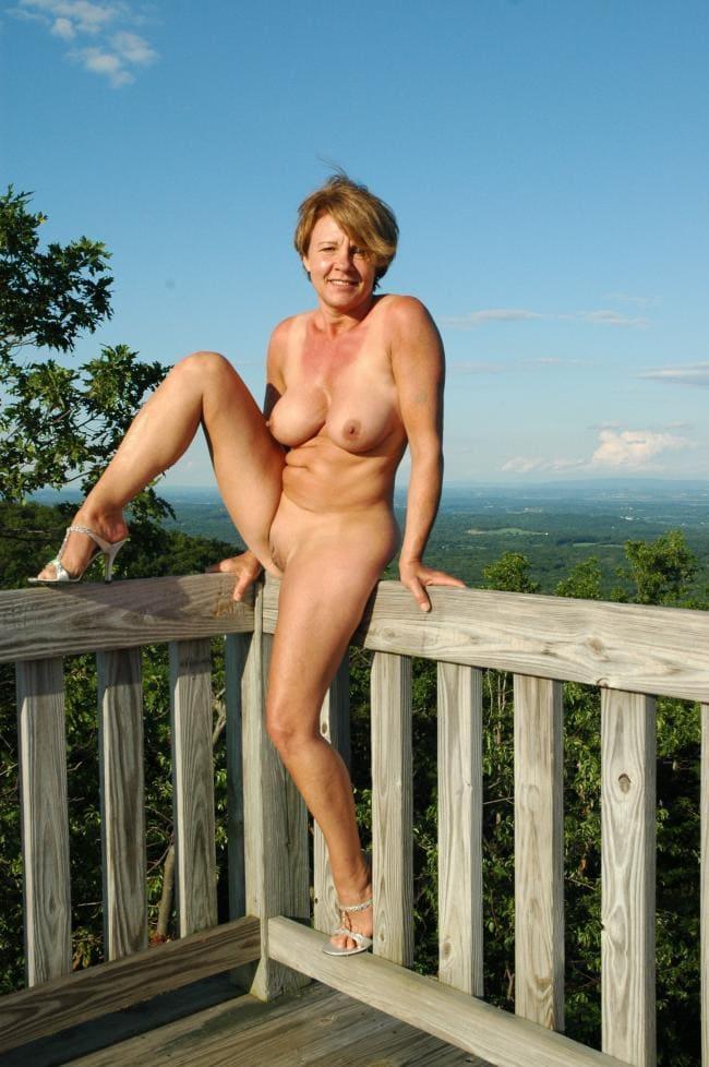 голые зрелые тетки фото сидит красивая женщина на перилах веранды полностью обнаженная в белых туфлях на высоком каблуке на закате и приветливо улыбается