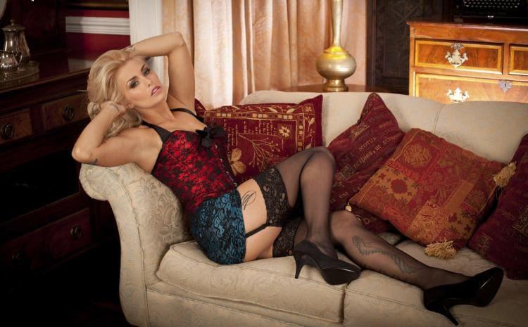 Зрелая блондинка, черные чулки на поясе, высокий каблук, ляжки и голень в татуировках