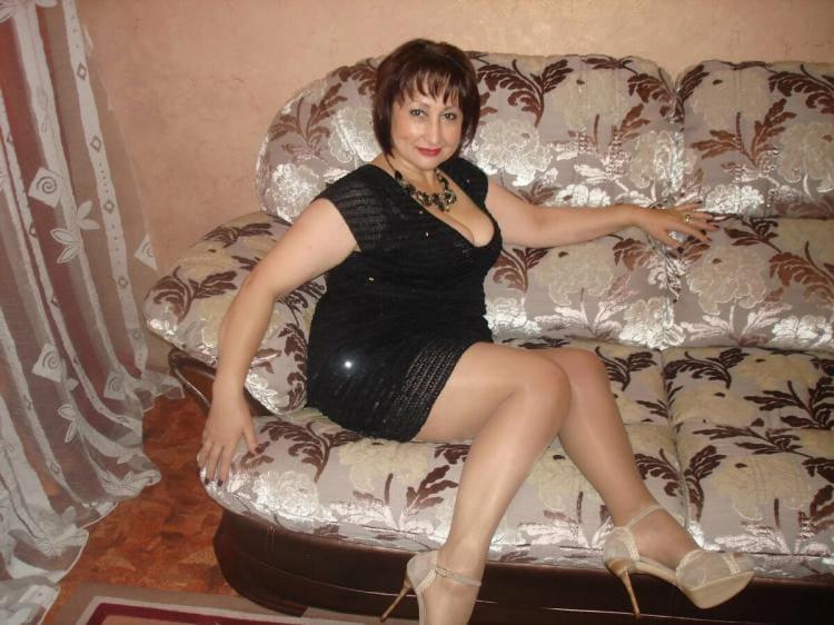 Зрелая в меру упитанная брюнетка с короткой стрижкой в коротком черном платье, блестящие колготки, туфли на высоком каблуке