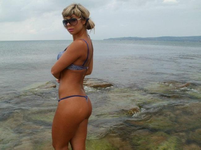 Шикарная зрелая блондинка в бикини стоит по колено в воде