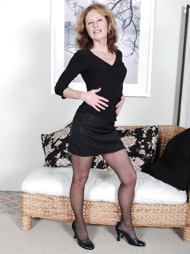Зрелая с хорошей фигурой в коротком черном платье в колготках туфлях