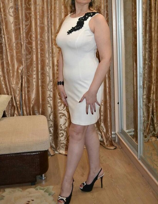 Зрелая в коротком платье стоит лица не видно, каблук