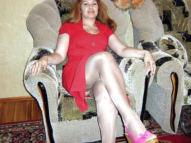 Зрелая рыжая в красном платье сидит в кресле вид снизу