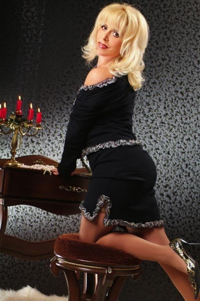 Блондинка в коротком платье стоит коленкой на стуле