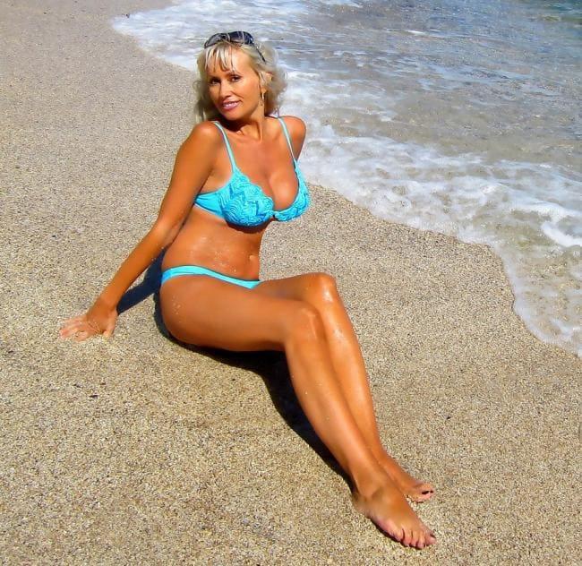Красивая зрелая блондинка в бирюзовом купальнике сидит на песке, шикарные ноги и ступни