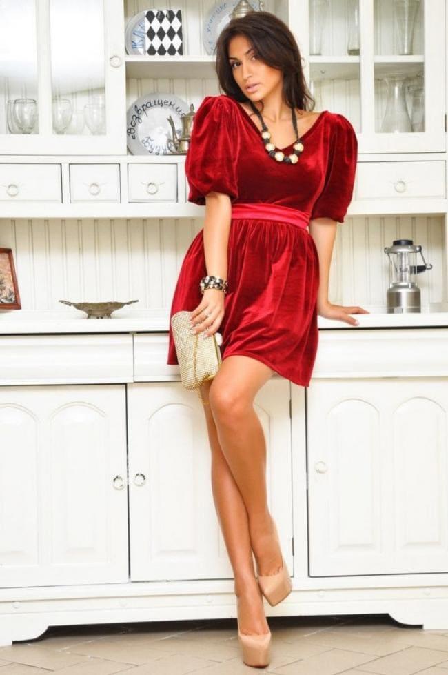 Красивая зрелая брюнетка в коротком красном платье стоит на кухне