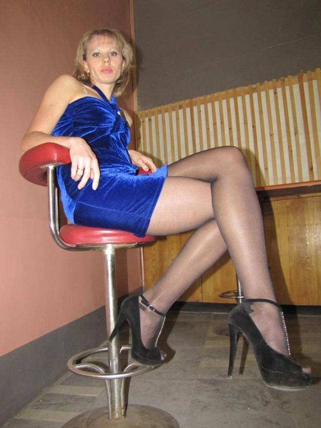 Зрелая тетя сидит на стуле в коротком платье и черных колготках вид ног снизу