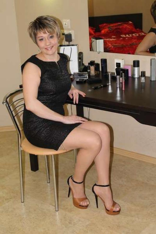 В черном коротком платье сидит на стуле каблуки