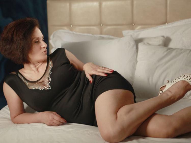 Брюнетка в коротком платье возлежит на диване