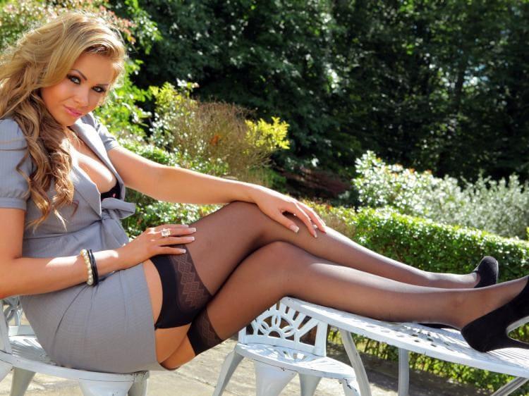 Красивая зрелая блондинка сидит на стуле в саду ноги на столе ,черные чулки на поясе. каблук, короткое платье, сиська выглядывает