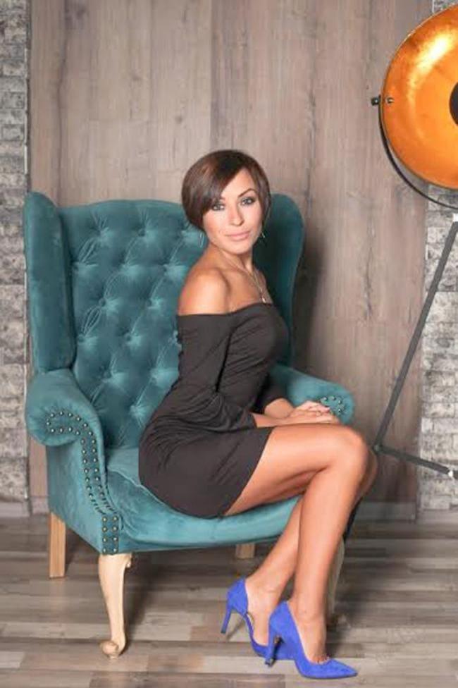 Зрелая в коротком платье плечи оголены восседает в кресле каблуки