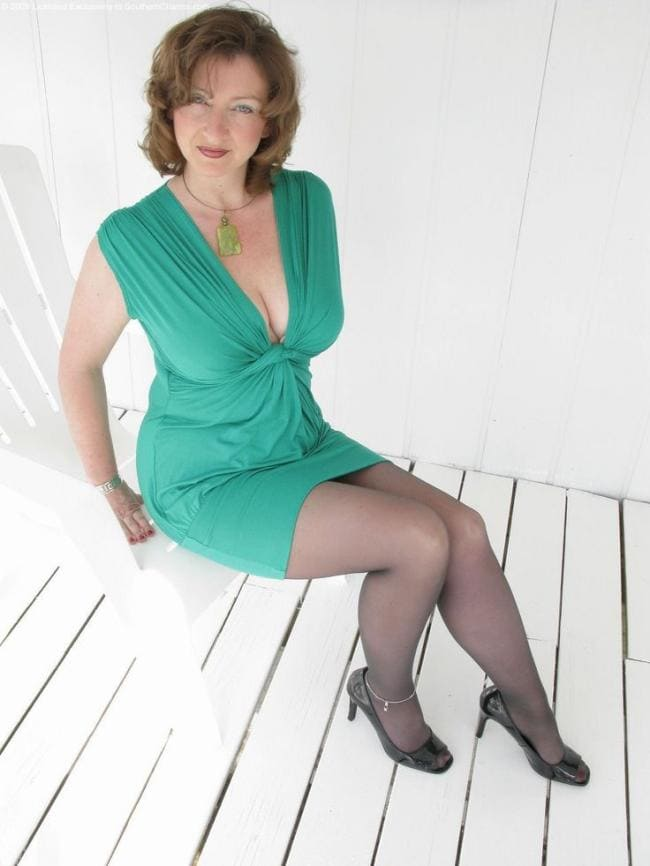 Зрелая красотка в зеленом платье декольте в колготках сидит на белом стуле