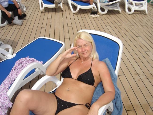 Зрелая Блондинка в черном бикини купальнике сидит в шезлонге