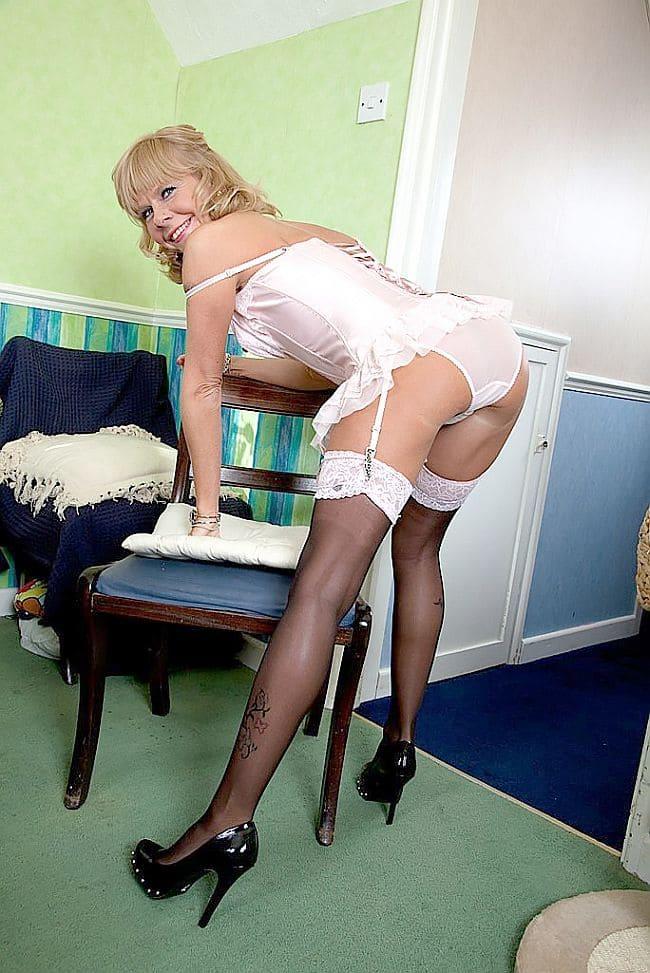 фото красивой зрелой мамки белом пеньюаре, в капроновых чулках стоит нагнувшись, ноги прямые в черных туфлях опирается на стул и приветливо улыбается повернув голову