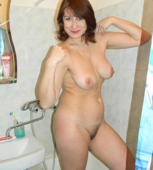 домашнее фото красивых зрелых женщин русская шатенка голая, сиськи торчат, пизда подстрижена, фигура стройная, стоит в душе, руки подняла и напрягла шутливо показывая какие у неё бицепсы, приветливо улыбается