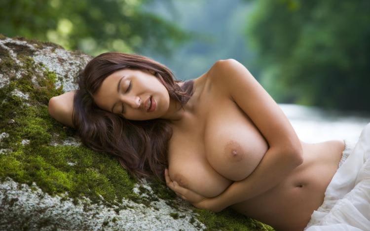 Голые сиськи девушек. Красавица лежит па берегу реки прикрыв глаза обняв свои сиси