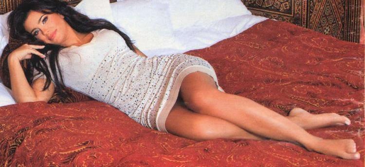 В белом коротком платье лежит на красном покрывале, ножки ступни